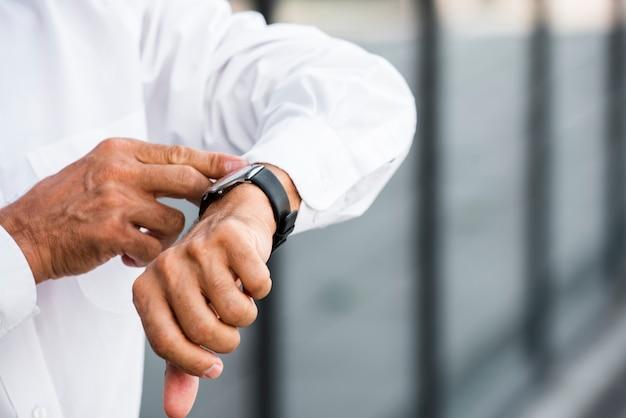 Empresário de close-up, olhando para o relógio de pulso