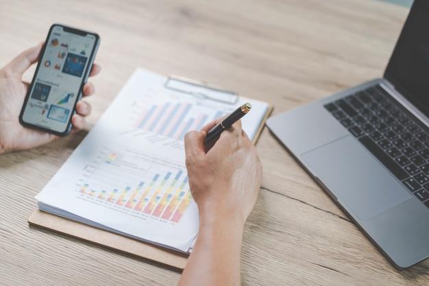Empresário de close-up segurando uma caneta, smartphone e apontando para o gráfico financeiro, verificando o relatório de negócios na mesa de madeira com o laptop do computador ao lado em casa. foto