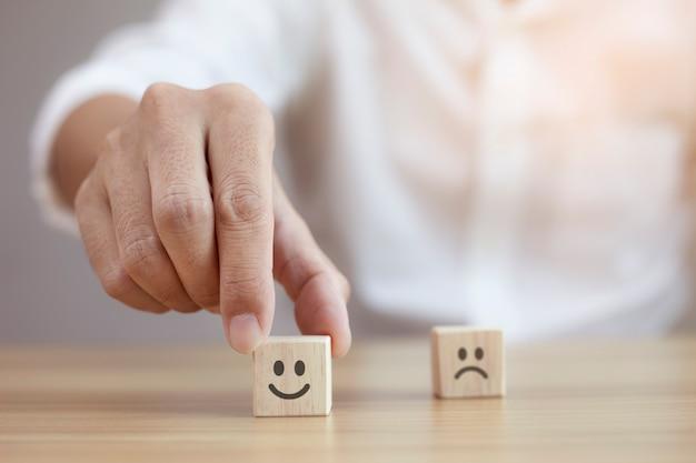 Empresário de closeup escolhe rosto sorridente e ícone de rosto triste desfocado no cubo de madeira