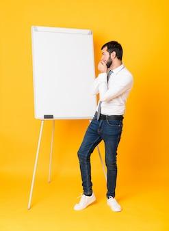 Empresário de comprimento total, dando uma apresentação no quadro branco sobre parede amarela isolada, cobrindo a boca e olhando para o lado