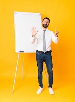 Empresário de comprimento total, dando uma apresentação no quadro branco sobre parede amarela isolada, contando seis com os dedos