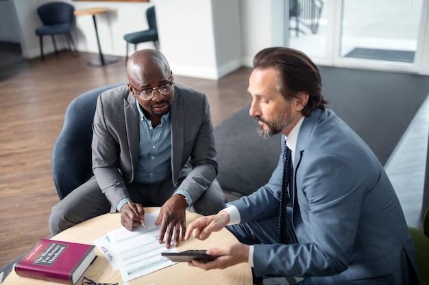 Empresário de consultoria. economista profissional de cabelos grisalhos consultando empresário no escritório