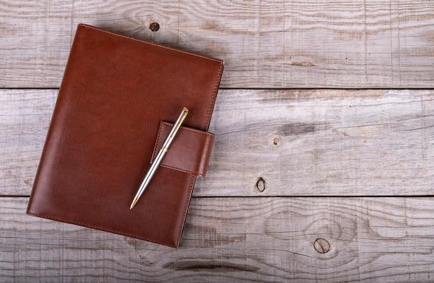 Empresário de couro e diário de caneta em fundo de madeira