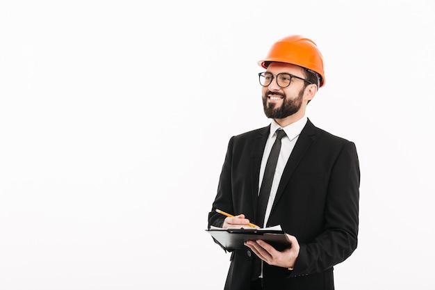 Empresário de engenheiro feliz no capacete, escrevendo notas.