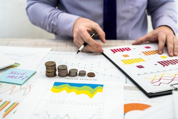 Empresário de escritório trabalhando e analisando os lucros da empresa usando gráficos e documentos usando moedas. análise de negócios e conceito de estratégia