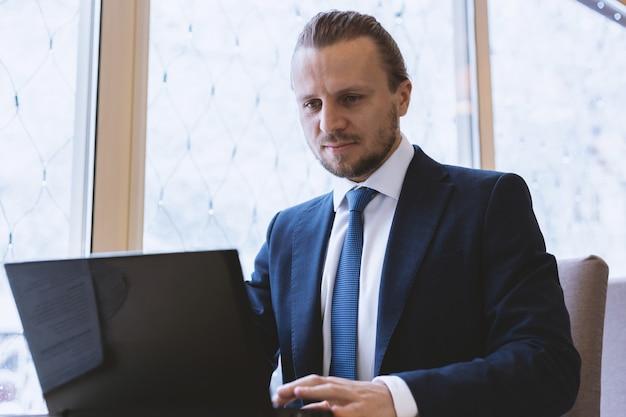 Empresário de fato trabalhando no laptop sentado à mesa coberta