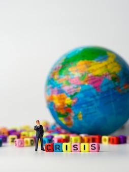 Empresário de figura em miniatura em pé parte traseira do colorido do alfabeto de crise e globo em segundo plano
