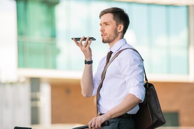 Empresário de gravata e camisa branca com smartphone ao lado da boca gravando mensagem enquanto está sentado na bicicleta e vai ao café depois do trabalho