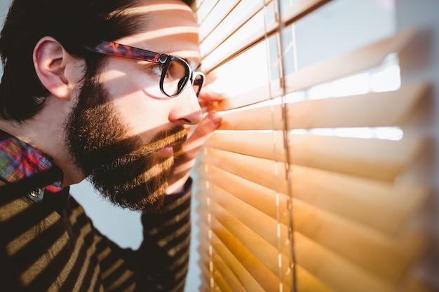Empresário de hipster espreitar através das cortinas