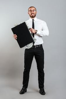 Empresário de homem rico de óculos e terno de negócio segurando o diplomata cheio de dinheiro dólar, isolado sobre parede cinza