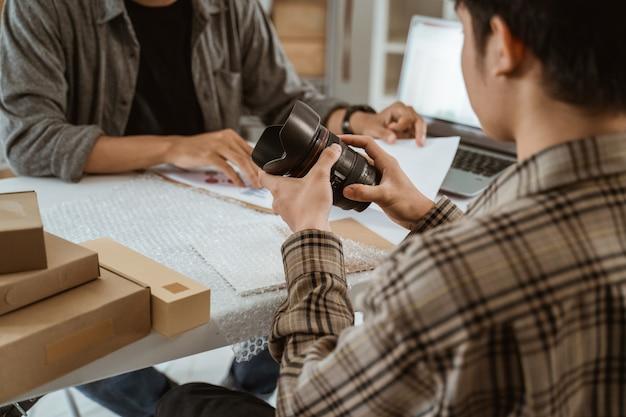 Empresário de jovens asiáticos conversando sobre a embalagem da lente da câmera