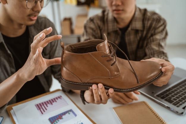 Empresário de jovens asiáticos conversando sobre o produto de sapatos
