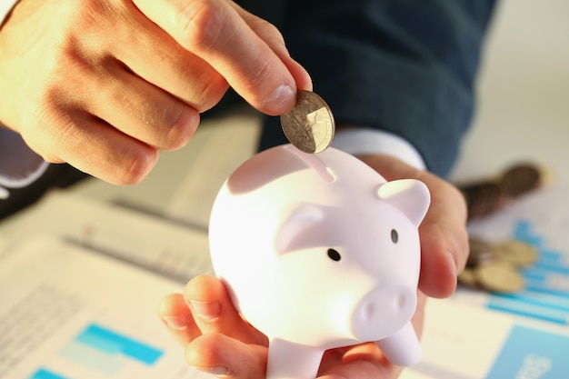 Empresário de mão colocando dinheiro pin no porco. necessidades futuras de empréstimo educação ou crédito hipotecário passam férias do sonho, efetivamente comprando o conceito de risco e segurança financeira