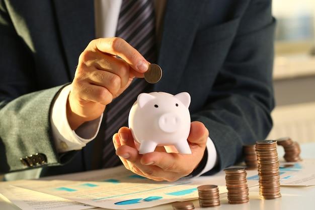 Empresário de mão colocando dinheiro pin no porco.