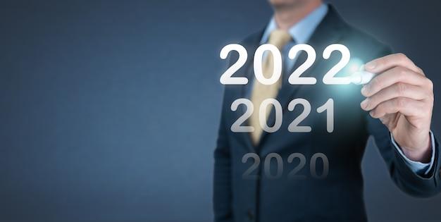 Empresário de mão escrevendo número 2022 na tela virtual. a meta de negócios e tecnologia estabelece metas e cumprimento na resolução de ano novo de 2022, planejamento e estratégias e ideias de inicialização
