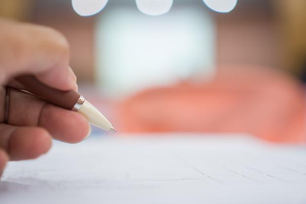 Empresário de mão segurando a caneta de prata para tomar notas em papelada branca ou documento na sala de reunião de conferência