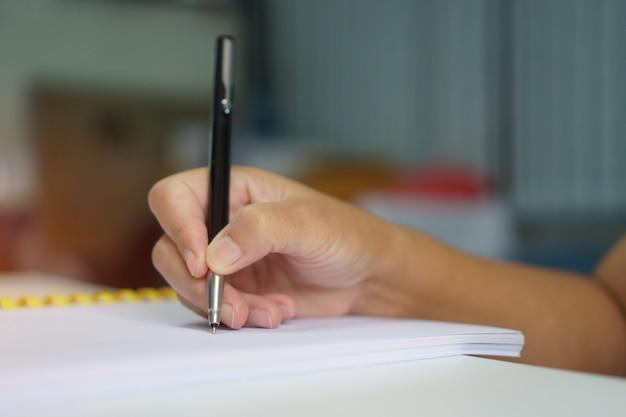 Empresário de mão segurando a caneta de prata para tomar notas em papelada branca