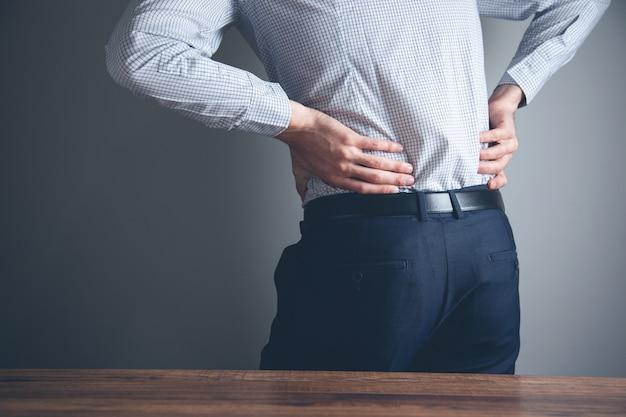 Empresário de mãos dadas com dor nas costas