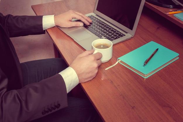 Empresário de mãos em um laptop