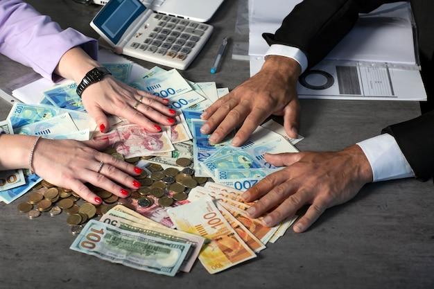 Empresário de mãos segurando e dando para um contrato um leque de dinheiro do novo shekel israelense, libras esterlinas e dólares. imagem recortada da mão segura notas. foco seletivo. as mãos de um homem e uma mulher seguram um dinheiro