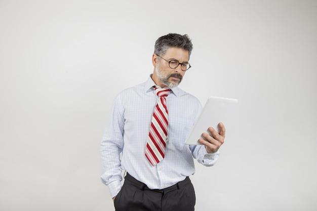 Empresário de meia-idade olhando para a tela em fundo branco