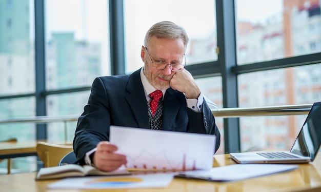 Empresário de meia idade pensativo de terno com um laptop na mesa enquanto trabalhava com documentos.