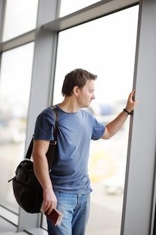 Empresário de meia idade segurando o passaporte e cartão de embarque
