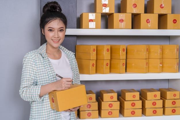 Empresário de mulher escrevendo na caixa de encomendas, negócios on-line, prepare antes da entrega