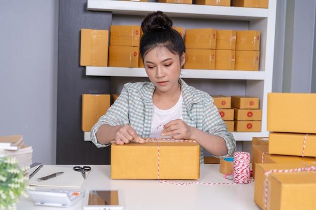 Empresário de mulher está amarrando cordas e produtos de embalagem na caixa de parcela