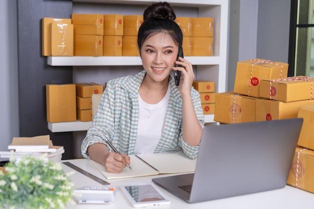 Empresário de mulher falando com o cliente no telemóvel e escrevendo a ordem do produto no escritório em casa