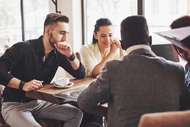 Empresário de multi étnica pessoas, conceito de pequenas empresas. mulher mostrando colegas de trabalho algo no computador portátil como eles se reúnem em torno de uma mesa de conferência