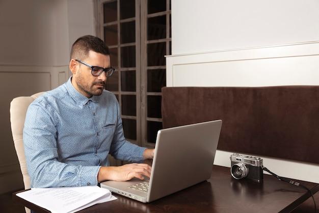 Empresário de óculos e camisa trabalhando em seu laptop em casa