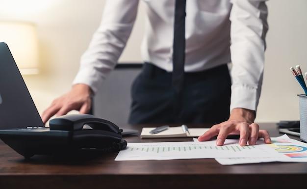 Empresário de pé e trabalhando no laptop com nota no livro no escritório à noite.