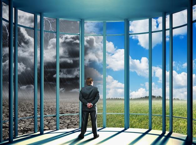 Empresário de pé no escritório olhando para a natureza mutável