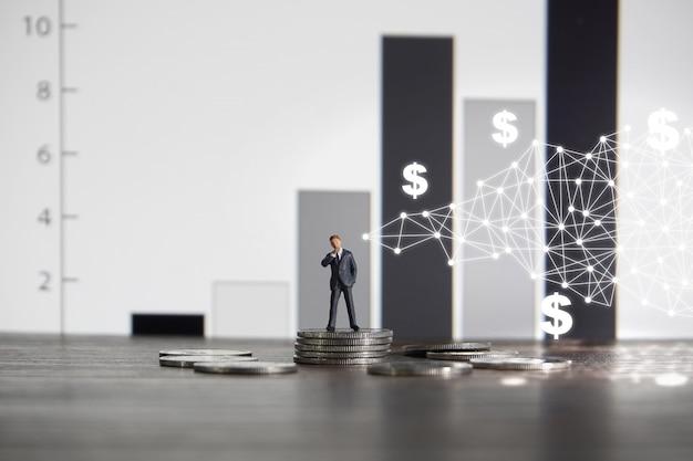 Empresário de pé sobre uma pilha de moedas