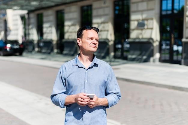 Empresário de quarenta anos de homem caucasiano com uma camisa parece para o lado, segurando um telefone.