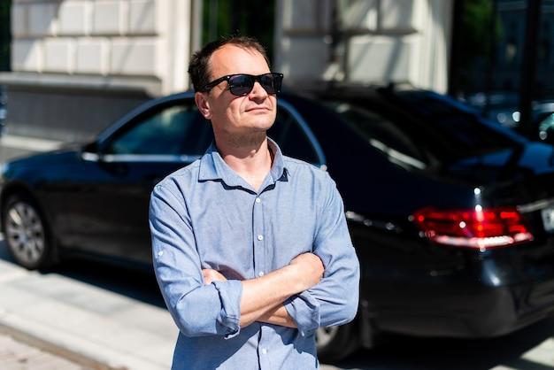 Empresário de quarenta anos de homem caucasiano na cidade no verão, no fundo do carro.