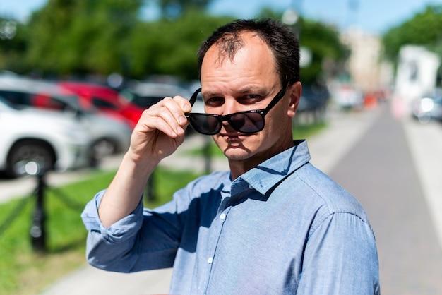 Empresário de quarenta anos de homem caucasiano na rua tira os óculos de sol.
