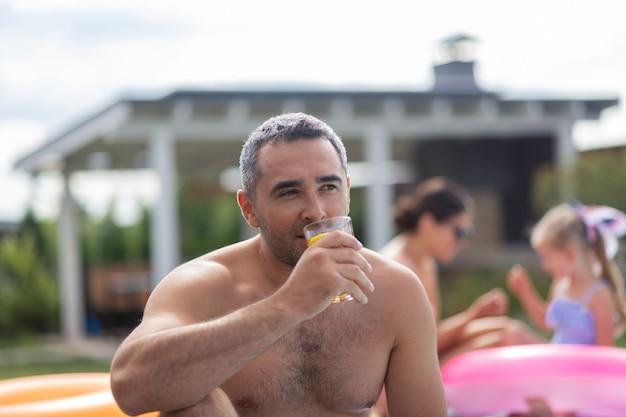 Empresário de refrigeração. empresário de olhos escuros relaxando perto da piscina com a família no fim de semana