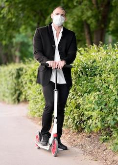 Empresário de retrato andando de scooter com máscara médica