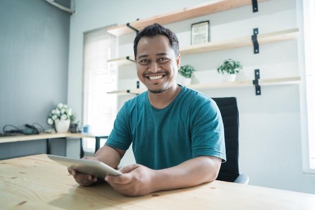Empresário de sorriso obter um sucesso para seus negócios e mãos segurando um tablet olhar para a câmera