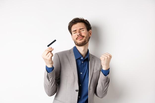 Empresário de sucesso animado dançando com cartão de crédito de plástico, levantando as bombas de punho e sorrindo encantado, de pé sobre um fundo branco no terno.