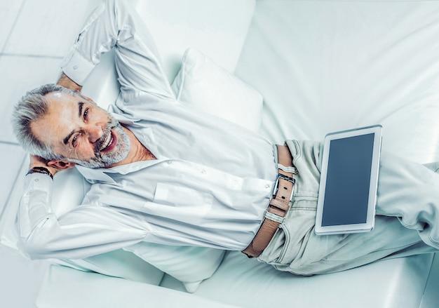 Empresário de sucesso com tablet digital sentado em um ambiente moderno