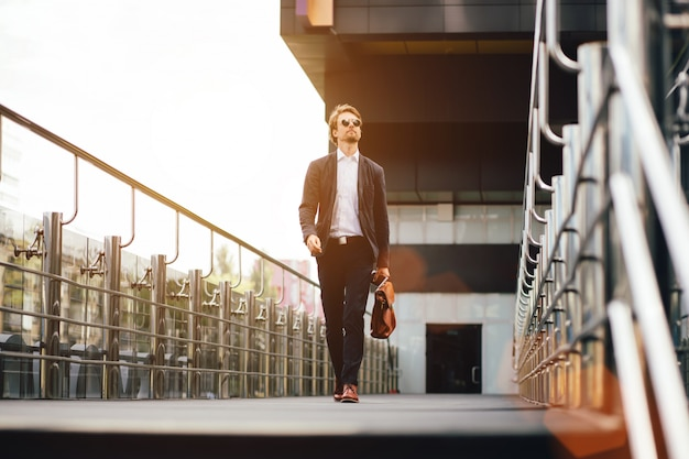 Empresário de sucesso com uma maleta na mão anda na rua no verão durante o pôr do sol