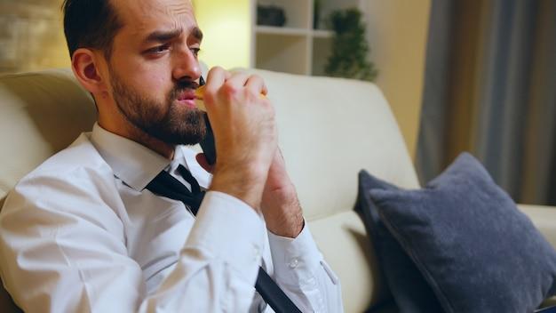 Empresário de sucesso comendo um hambúrguer sentado no sofá após um dia cansativo e falando ao telefone.