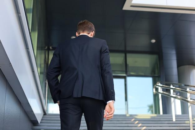 Empresário de sucesso elegante sobe as escadas do prédio de escritórios.