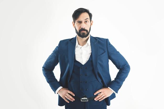 Empresário de sucesso em um terno de negócio e em pé com as mãos no cinto. a foto tem um espaço vazio para o seu texto