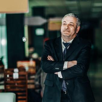 Empresário de sucesso em um terno de negócio no fundo de um escritório moderno