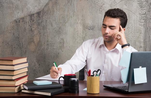 Empresário de sucesso escrevendo papéis de trabalho na mesa do escritório.