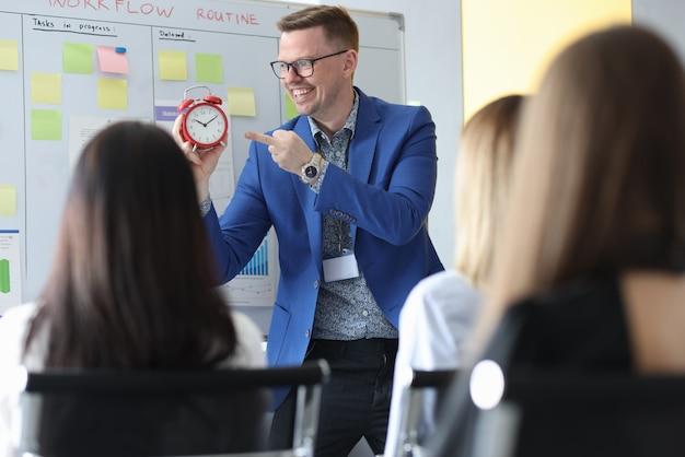 Empresário de sucesso falando na conferência e mostrando as horas no despertador vermelho